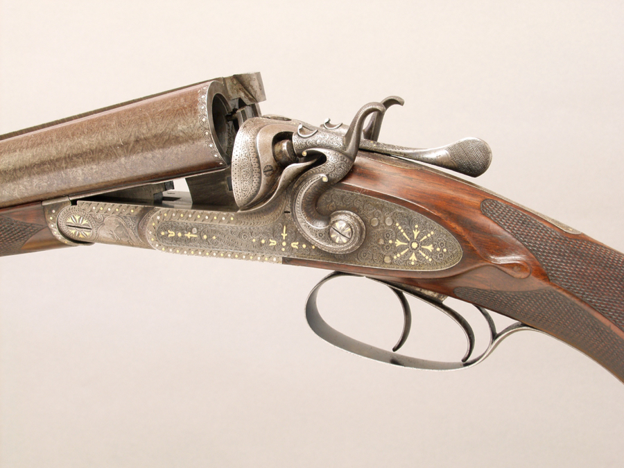 An early example of the company's high-grade guns, this thoroughly embellished 12-gauge, Serial No. 126, features back-action locks of the maker's patent and a  cloverleaf-shape doll's-head slotted for a third fastener.